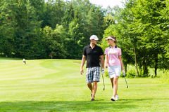 Young sportive couple playing golf on a course. Young sportive couple playing golf on a golf course, they walking to the next hole Stock Photos