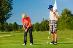 Young sportive couple playing golf on a course Royalty Free Stock Photography