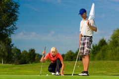 Young sportive couple playing golf on a course. Young female golf player on course putting, she aiming for her put shot Stock Photo