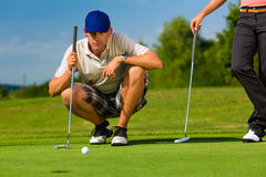Young sportive couple playing golf on a course. Young golf player on course putting, he aiming for his put shot Stock Photos
