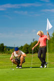 Young sportive couple playing golf on a course. Young golf player on course putting, he aiming for his put shot Stock Photo
