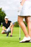 Young sportive couple playing golf on a course Royalty Free Stock Photos