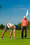 Young sportive couple playing golf on a course stock photos