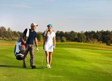 Young sportive couple playing golf. On a golf course walking to the next hole Royalty Free Stock Image
