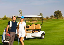 Young sportive couple playing golf on a golf course Stock Images