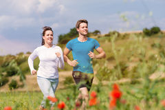 Young sportive couple is running outside Stock Images