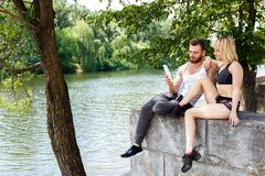 Young sportive couple sitting on a park near a river, use intern. Young sportive couple sitting on a park near a river. Beautiful girl and men use internet on Royalty Free Stock Photography