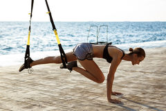Young sportive girl training with trx near sea in the morning. Young beautiful sportive girl training with trx near sea Stock Photography