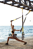 Young sportive girl training with trx near sea in the morning. Young beautiful sportive people training with trx near sea Stock Images