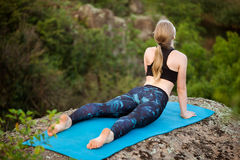 Young sportive girl training yoga asanas on rock in canyon. Stock Photo
