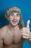 Young sportive handsome man in stylish hipster fur hat with crazy emotions agree and smile, shows the gesture OK Royalty Free Stock Photography