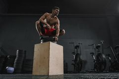 Young sportive man resting after box jump exercise at the gym stock image
