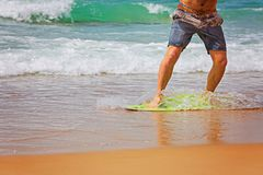 Young sportive man is running after his yellow and blue skimboard on the beach on a sunny day.  Stock Images