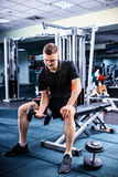 Young sportive man in sportswear lifting some weights. And working on his biceps in a gym Royalty Free Stock Image