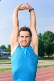 Young sportive man stretching his arms Royalty Free Stock Photos