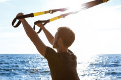 Young sportive man training with trx near sea in the morning. Young sportive handsome man training with trx near sea Royalty Free Stock Photo