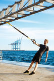 Young sportive man training with trx near sea in the morning. Stock Photography
