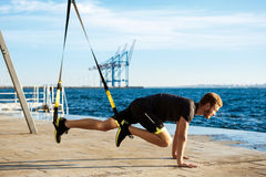 Young sportive man training with trx near sea in the morning. Royalty Free Stock Images