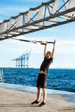 Young sportive man training with trx near sea in the morning. Stock Photo