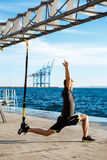 Young sportive man training with trx near sea in the morning. Young sportive handsome man training with trx near sea Royalty Free Stock Photography