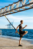 Young sportive man training with trx near sea in the morning. Royalty Free Stock Photos