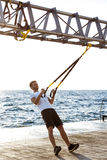 Young sportive man training with trx near sea in the morning. Royalty Free Stock Image