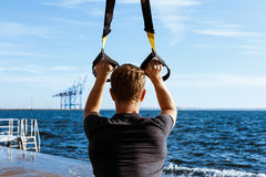 Young sportive man training with trx near sea in the morning. Young sportive handsome man training with trx near sea Royalty Free Stock Images