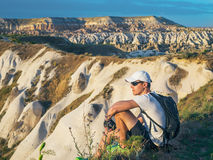 Young sportive man in white cap with backpack sitting on the peak of sandstone rock and watching nature landscapes. Cappadocia, Turkey Royalty Free Stock Photos
