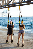 Young sportive people training with trx near sea in the morning. Stock Photography