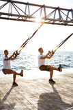 Young sportive people training with trx near sea in the morning. Young beautiful sportive people training with trx near sea Stock Images