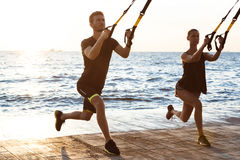 Young sportive people training with trx near sea in the morning. Young beautiful sportive people training with trx near sea Stock Photos