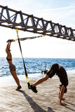 Young sportive people training with trx near sea in the morning. Young beautiful sportive people training with trx near sea Royalty Free Stock Photo