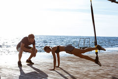 Young sportive people training with trx near sea in the morning. Young beautiful sportive people training with trx near sea Royalty Free Stock Photography