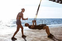 Young sportive people training with trx near sea in the morning. Young beautiful sportive people training with trx near sea Royalty Free Stock Photos