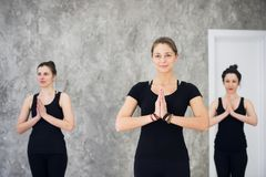 Young sportive trio group of girls are practicing yoga exercises in the studio Stock Photography