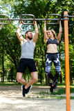 Young sportive woman and bearded man doing pull-ups exercises on Royalty Free Stock Image