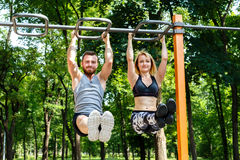 Young sportive woman and bearded man doing pull-ups exercises on Royalty Free Stock Images