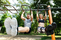 Young sportive woman and bearded man doing pull-ups exercises on Stock Photo