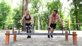 Young sportive woman and bearded man doing push-ups exercises in a parrk. stock video