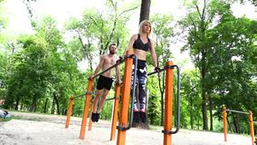 Young sportive woman and bearded man doing push-ups exercises in a parrk. stock footage