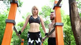 Young sportive woman and bearded man doing push-ups exercises in a parrk. stock video footage