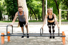 Young sportive woman and bearded man doing push-ups exercises in Royalty Free Stock Photos