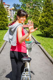 Young sportive woman with bike waving Stock Photo