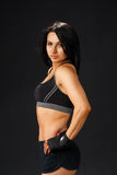 Young sportive woman at black background Stock Photo