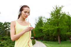 Young sportive woman choosing music in park Royalty Free Stock Image
