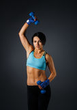 Young sportive woman with dumbbells at grey background Royalty Free Stock Photo