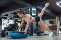 Concentrated woman training with equipment in gym royalty free stock photography