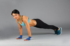 Young sportive woman makes fitness push up Royalty Free Stock Photography