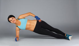 Young sportive woman makes side plank at grey background Stock Photo