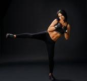 Young sportive woman makes tae bo side leg kick Stock Photography